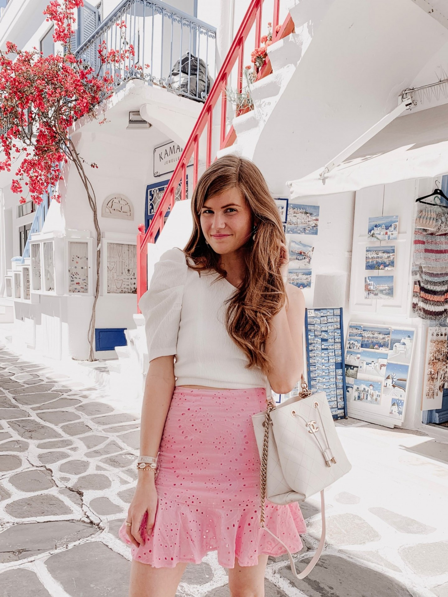 Mykonos Travel Guide featured by top London travel blogger Mollie Moore; Image of a woman wearing a white top and pink skirt.