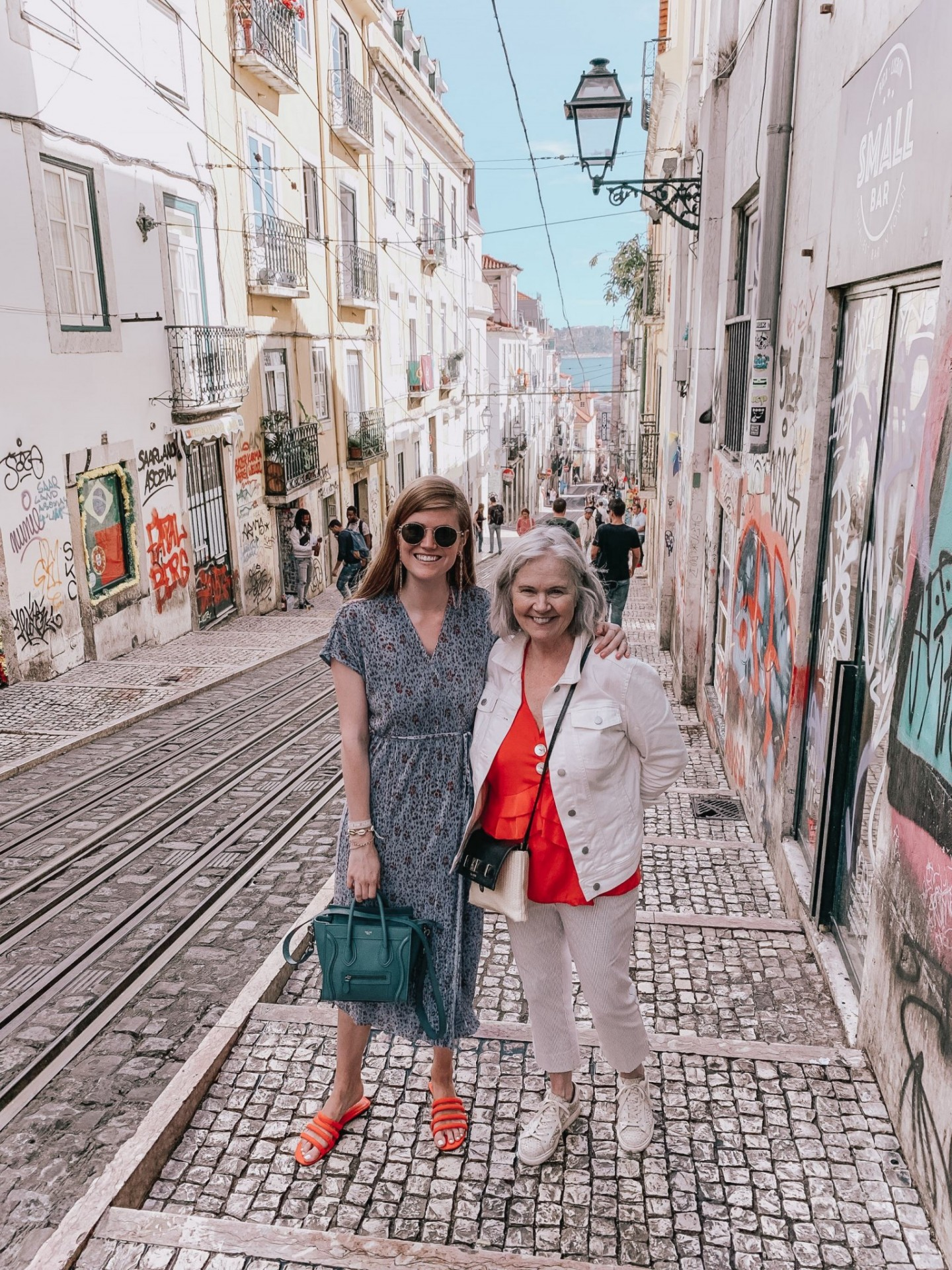 Lifestyle blogger Mollie Moore shares a Lisbon travel guide | Visiting Portugal: The Ultimate Lisbon Travel Guide & the Best Things to Do by popular London travel blogger, Mollie Moore: image of two women standing in an alley with lots of graffiti in Lisbon, Portugal.