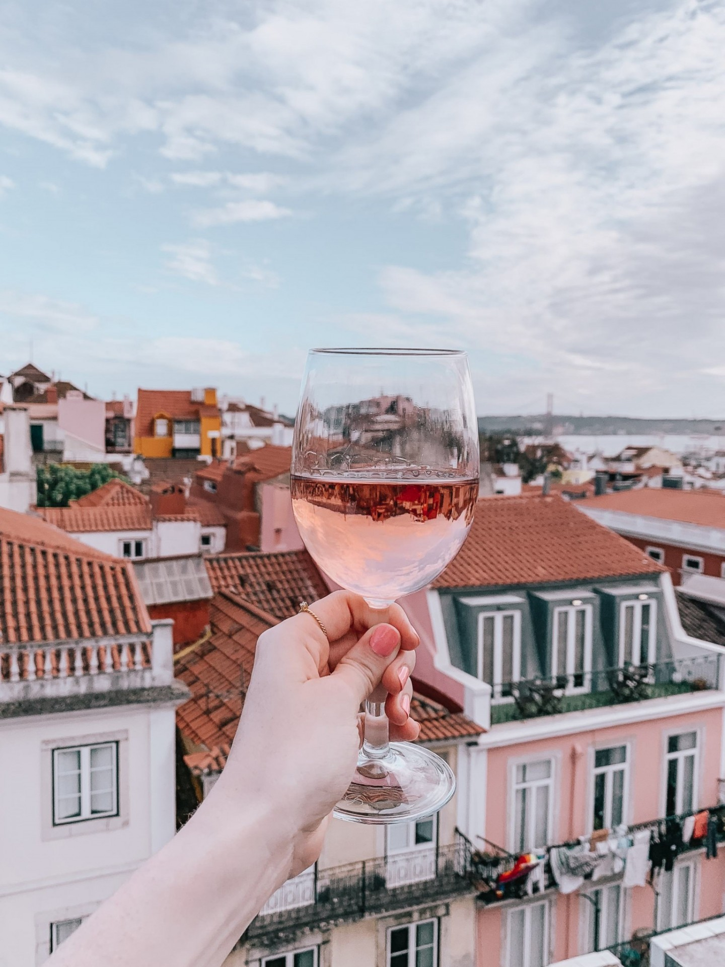 Lifestyle blogger Mollie Moore shares a Lisbon travel guide | Visiting Portugal: The Ultimate Lisbon Travel Guide & the Best Things to Do by popular London travel blogger, Mollie Moore: image of a woman's hand holding a glass of wine with the reflection of Lisbon, Portugal in it.