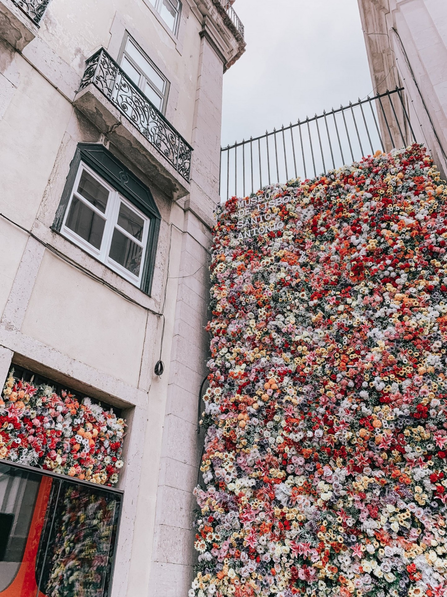 Lifestyle blogger Mollie Moore shares a Lisbon travel guide | Visiting Portugal: The Ultimate Lisbon Travel Guide & the Best Things to Do by popular London travel blogger, Mollie Moore: image of a flower wall in Lisbon, Portugal.