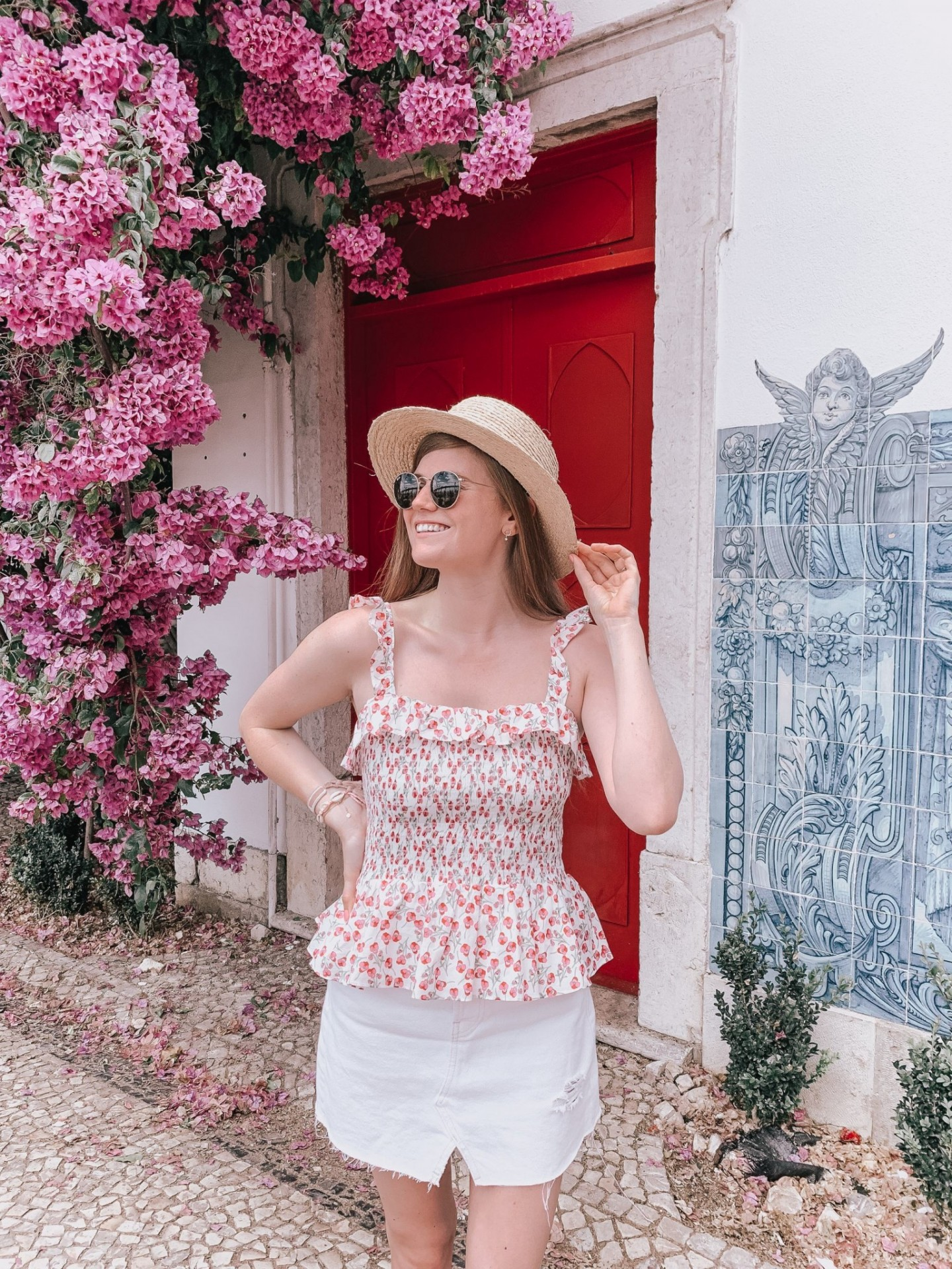 Lifestyle blogger Mollie Moore shares a Lisbon travel guide | Visiting Portugal: The Ultimate Lisbon Travel Guide & the Best Things to Do by popular London travel blogger, Mollie Moore: image of a woman standing next to a pink flowering trellis bush that's growing up the side of building with a red door.
