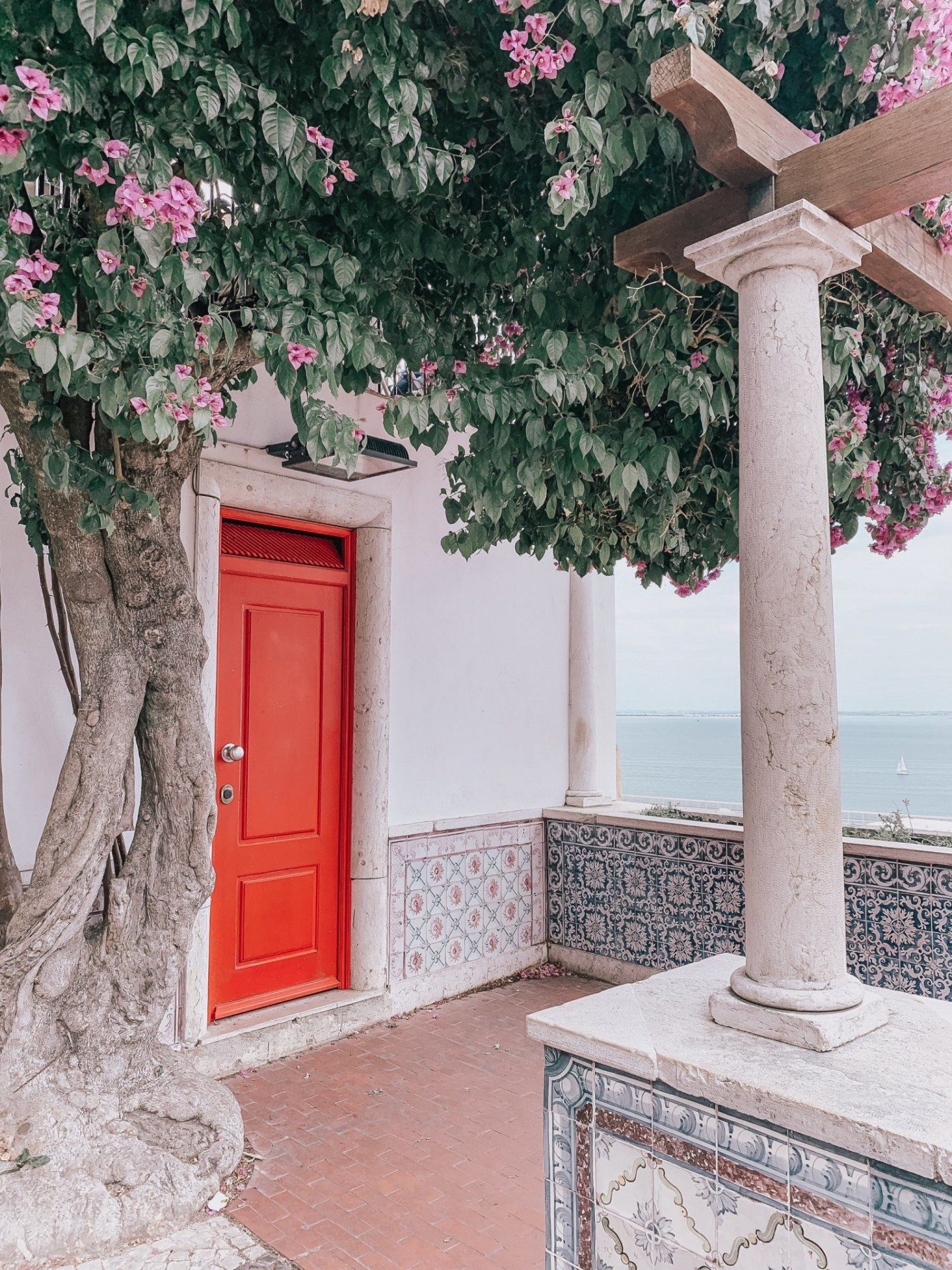 Lifestyle blogger Mollie Moore shares a Lisbon travel guide   Visiting Portugal: The Ultimate Lisbon Travel Guide & the Best Things to Do by popular London travel blogger, Mollie Moore: image of a building with a red door.