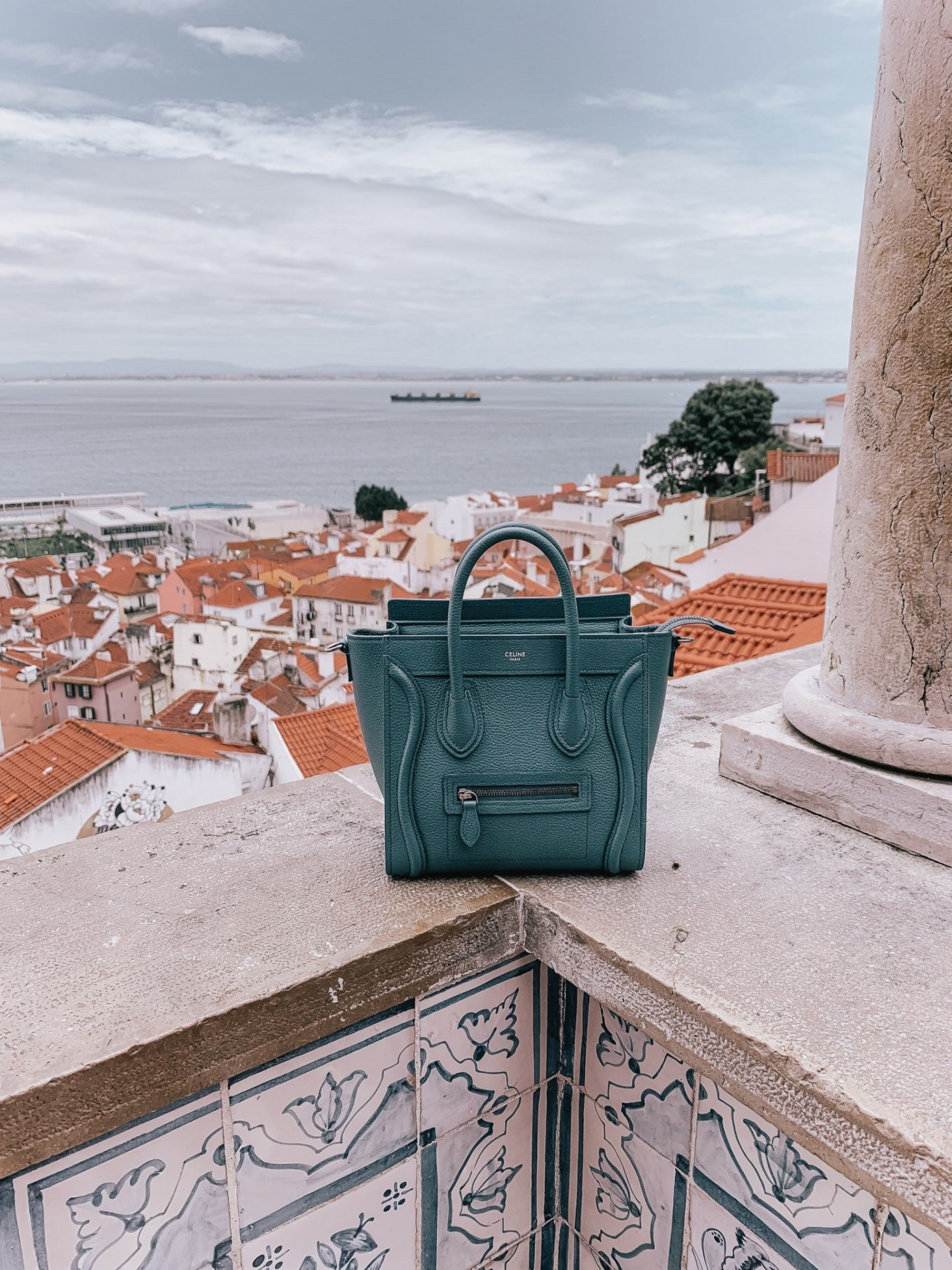 Lifestyle blogger Mollie Moore shares a Lisbon travel guide | Visiting Portugal: The Ultimate Lisbon Travel Guide & the Best Things to Do by popular London travel blogger, Mollie Moore: image of a Celine bag on a balcony with the city of Lisbon, Portugal in the distance.