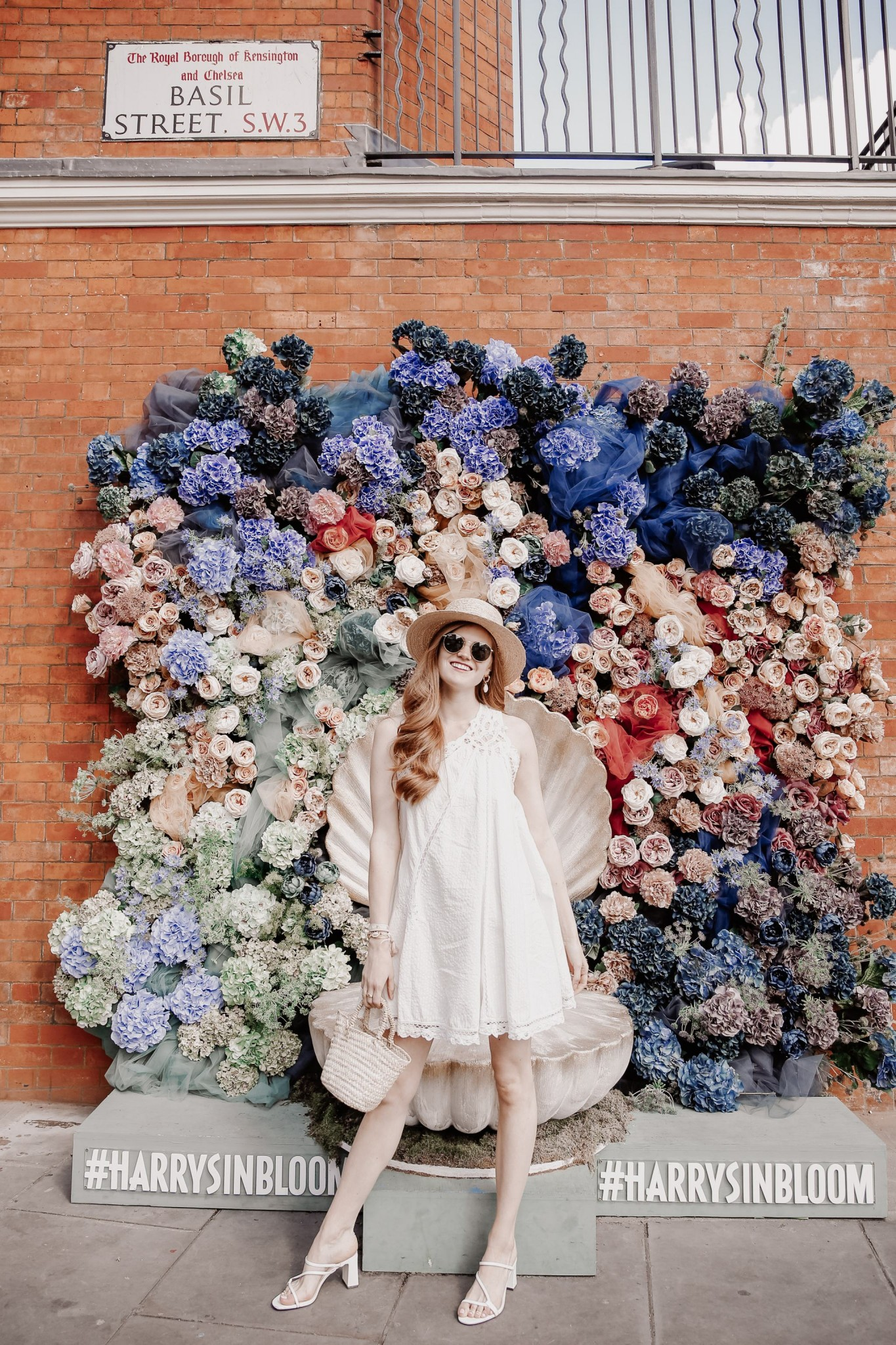Lifestyle blogger Mollie Moores shares her favorite white dresses for summer   LWD: The Free People Little White Dress by popular London fashion blogger, Mollie Moore: image of a woman standing in front of a floral backdrop wearing a Free People Billie Battenburg One-Shoulder Dress.