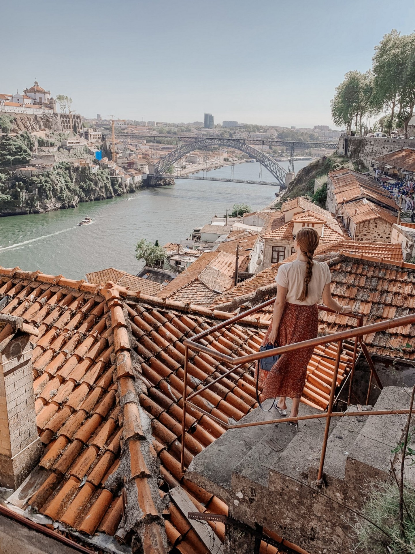 Lifestyle blogger Mollie Moore shares a Porto travel guide | A Porto Portugal Travel Guide by popular Great Britain international travel blogger, Mollie Moore: image of a woman standing on a stair case outside surrounded by red tile roof buildings and overlooking a river and the city of Porto Portugal.