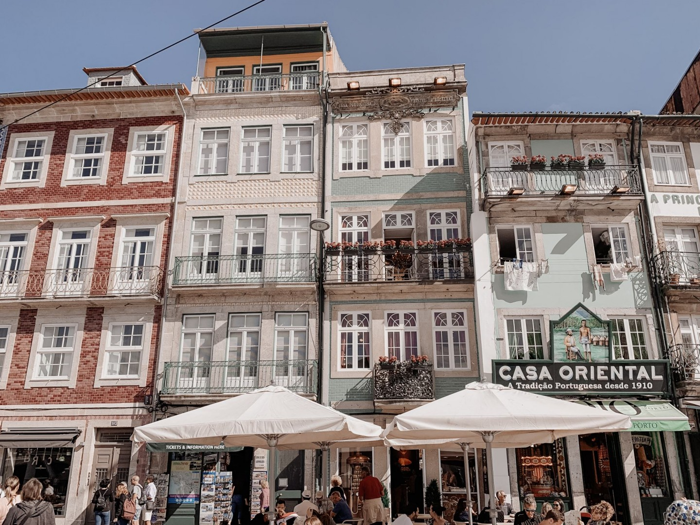 Lifestyle blogger Mollie Moore shares a Porto travel guide | A Porto Portugal Travel Guide by popular Great Britain international travel blogger, Mollie Moore: image of different colored building fronts, cafe tables with tan umbrellas, and Casa Oriental.