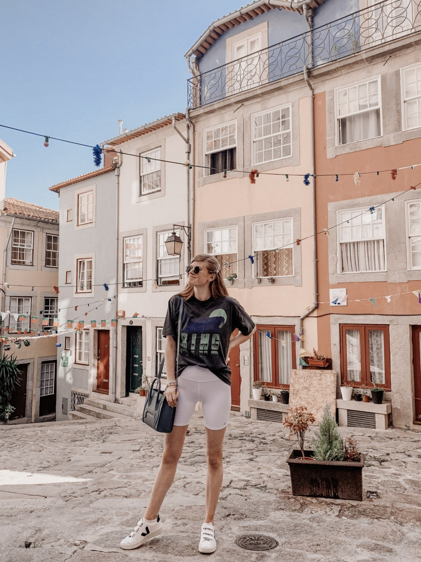 Lifestyle blogger Mollie Moore shares a Porto travel guide | A Porto Portugal Travel Guide by popular Great Britain international travel blogger, Mollie Moore: image of a woman standing on a cobble stone street surrounded by colorful buildings with pennant banners strung overhead.