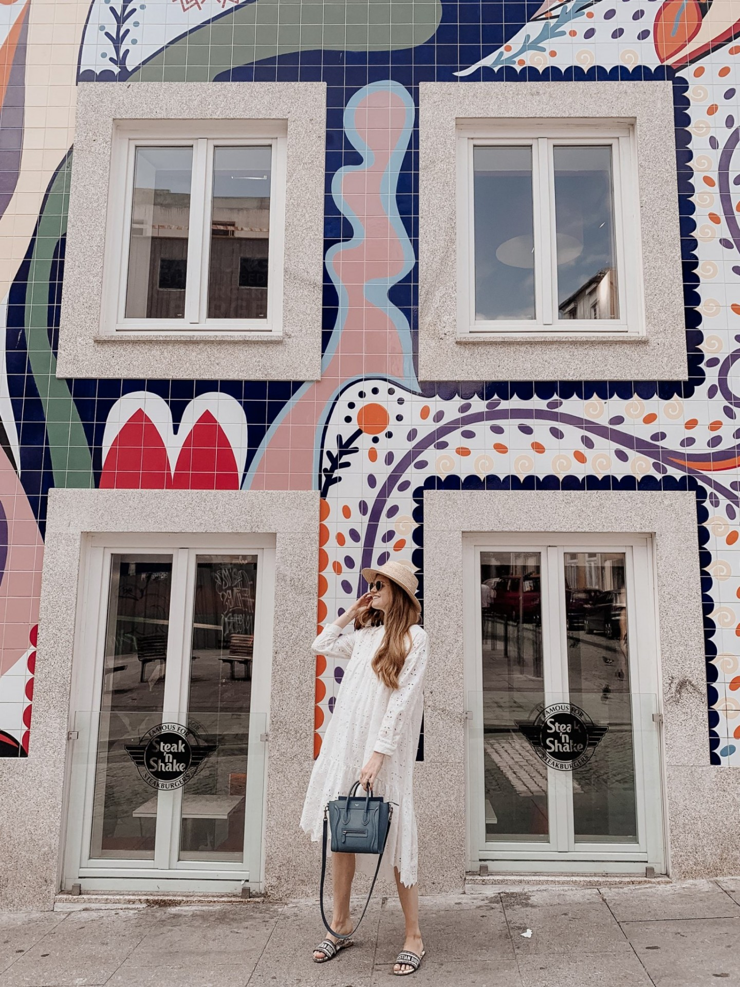 Lifestyle blogger Mollie Moore shares a Porto travel guide | A Porto Portugal Travel Guide by popular Great Britain international travel blogger, Mollie Moore: image of a woman standing in front of a stake n' shake building with a large tile mosaic in Porto Portugal.