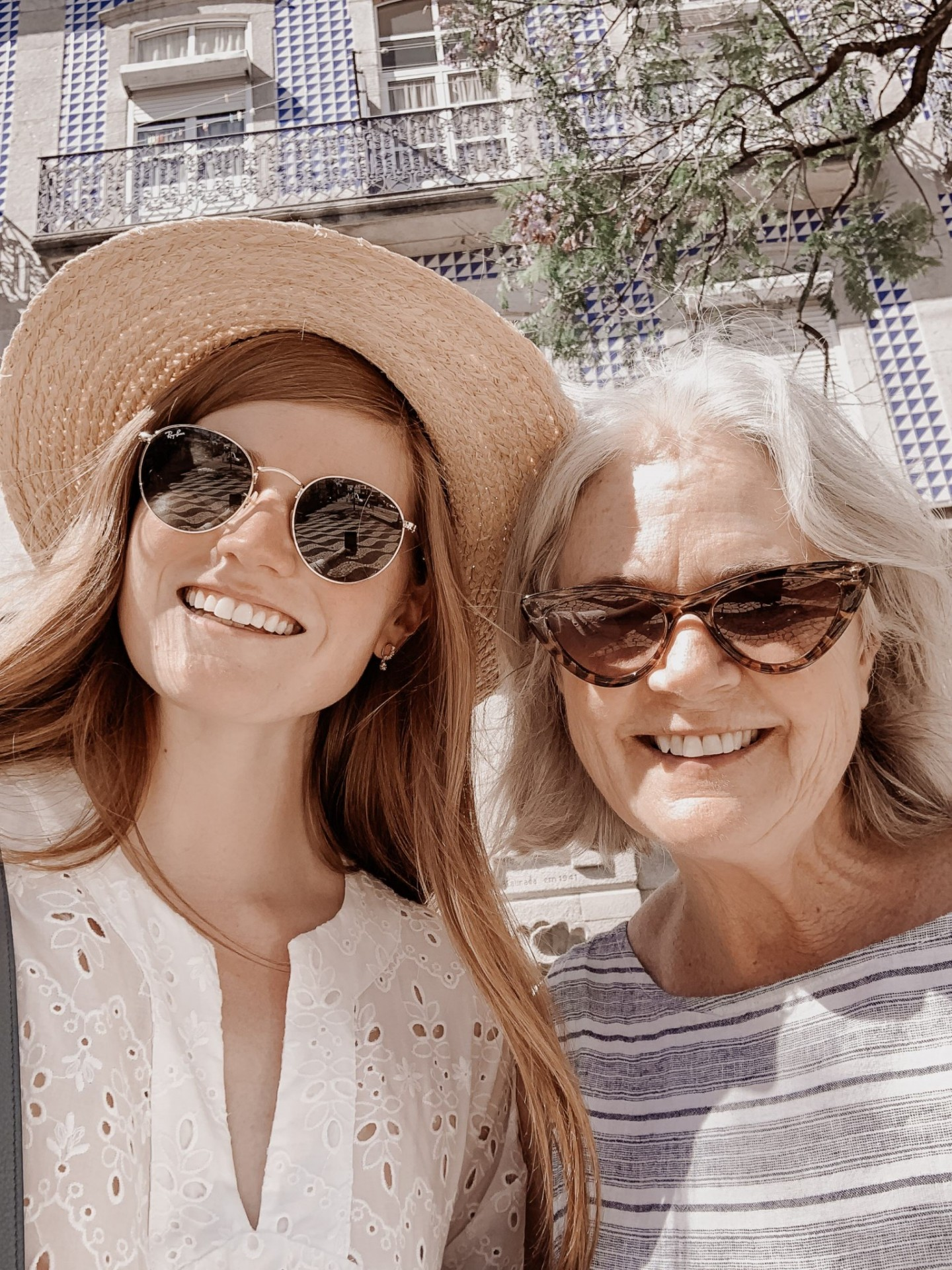 Lifestyle blogger Mollie Moore shares a Porto travel guide | A Porto Portugal Travel Guide by popular Great Britain international travel blogger, Mollie Moore: image of two women standing in front of a blue and white tile building in Porto Portugal.