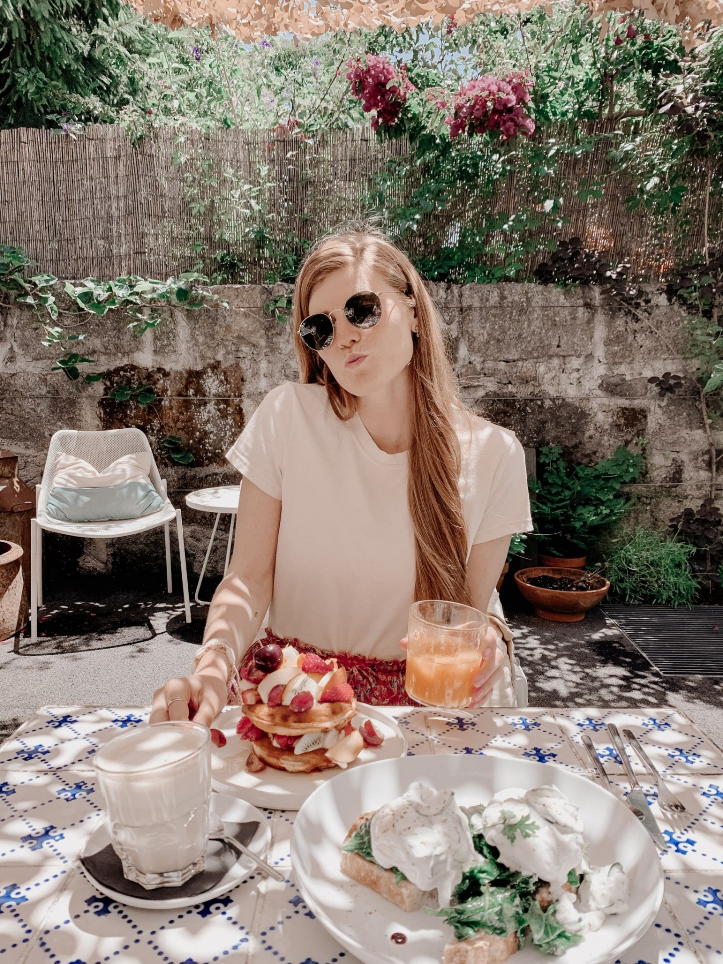 Lifestyle blogger Mollie Moore shares a Porto travel guide   A Porto Portugal Travel Guide by popular Great Britain international travel blogger, Mollie Moore: image of a woman sitting at a blue and white tile table and eating waffles with cream and berries.
