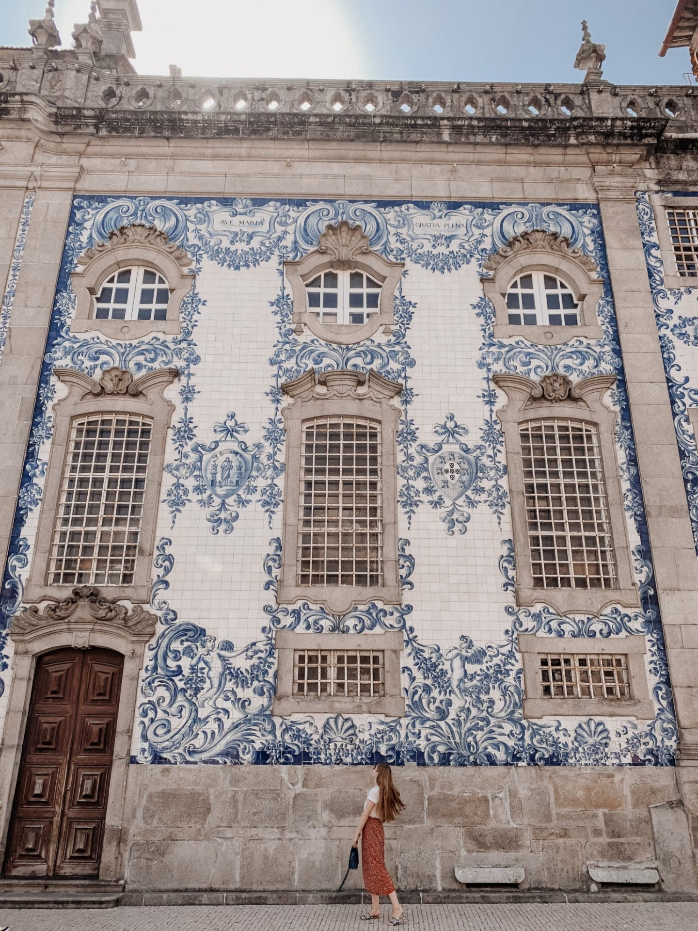 Lifestyle blogger Mollie Moore shares a Porto travel guide | A Porto Portugal Travel Guide by popular Great Britain international travel blogger, Mollie Moore: image of a woman standing in front of a blue and white tile building in Porto Portugal.