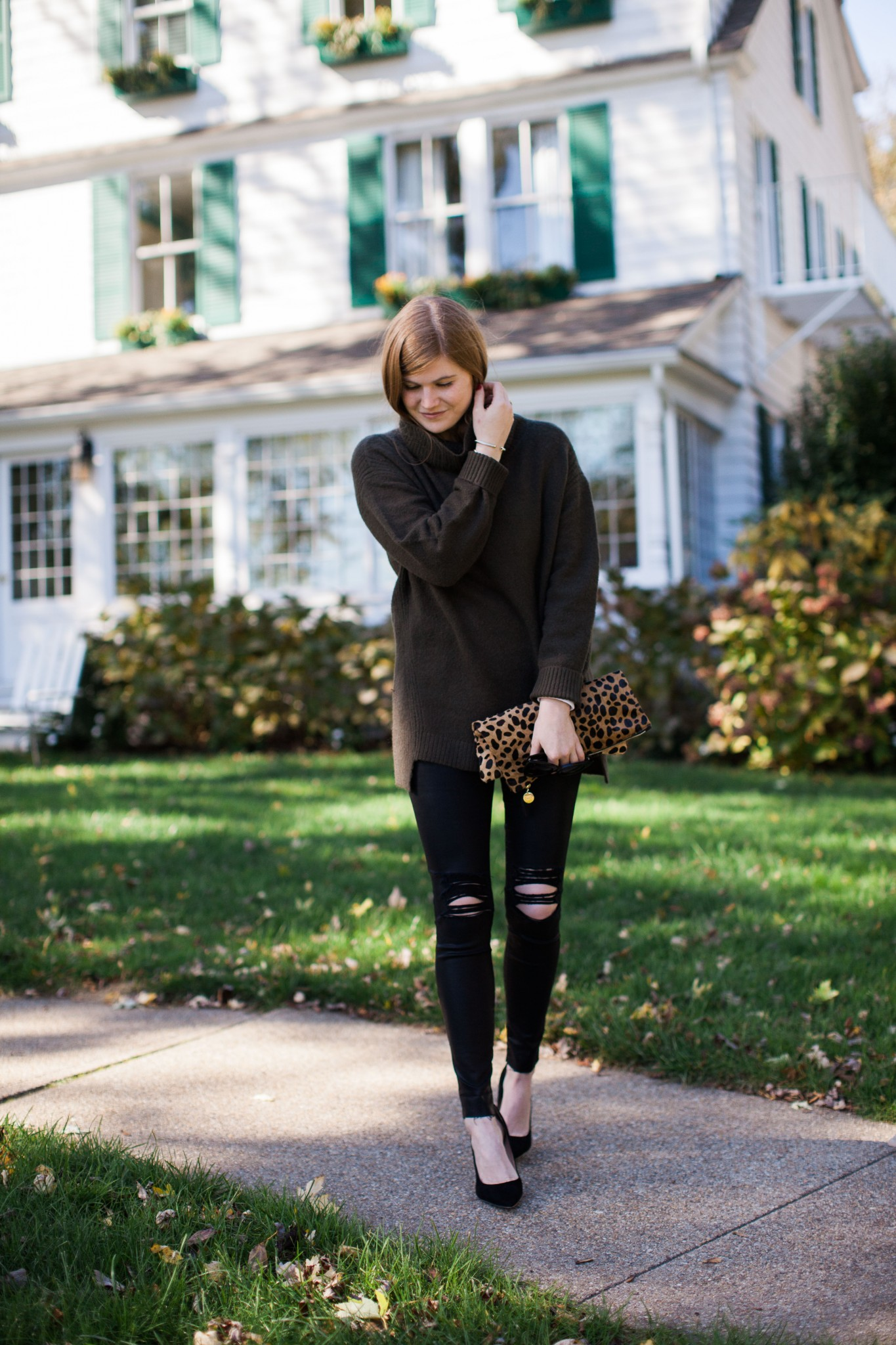 Thanksgiving Outfit Idea featured by top London fashion blogger, Mollie Moore: picture of a woman wearing an oversized turtleneck sweater, The Icon skinny jeans, Sam Edelman heels, leopard clutch, cat eye sunglasses