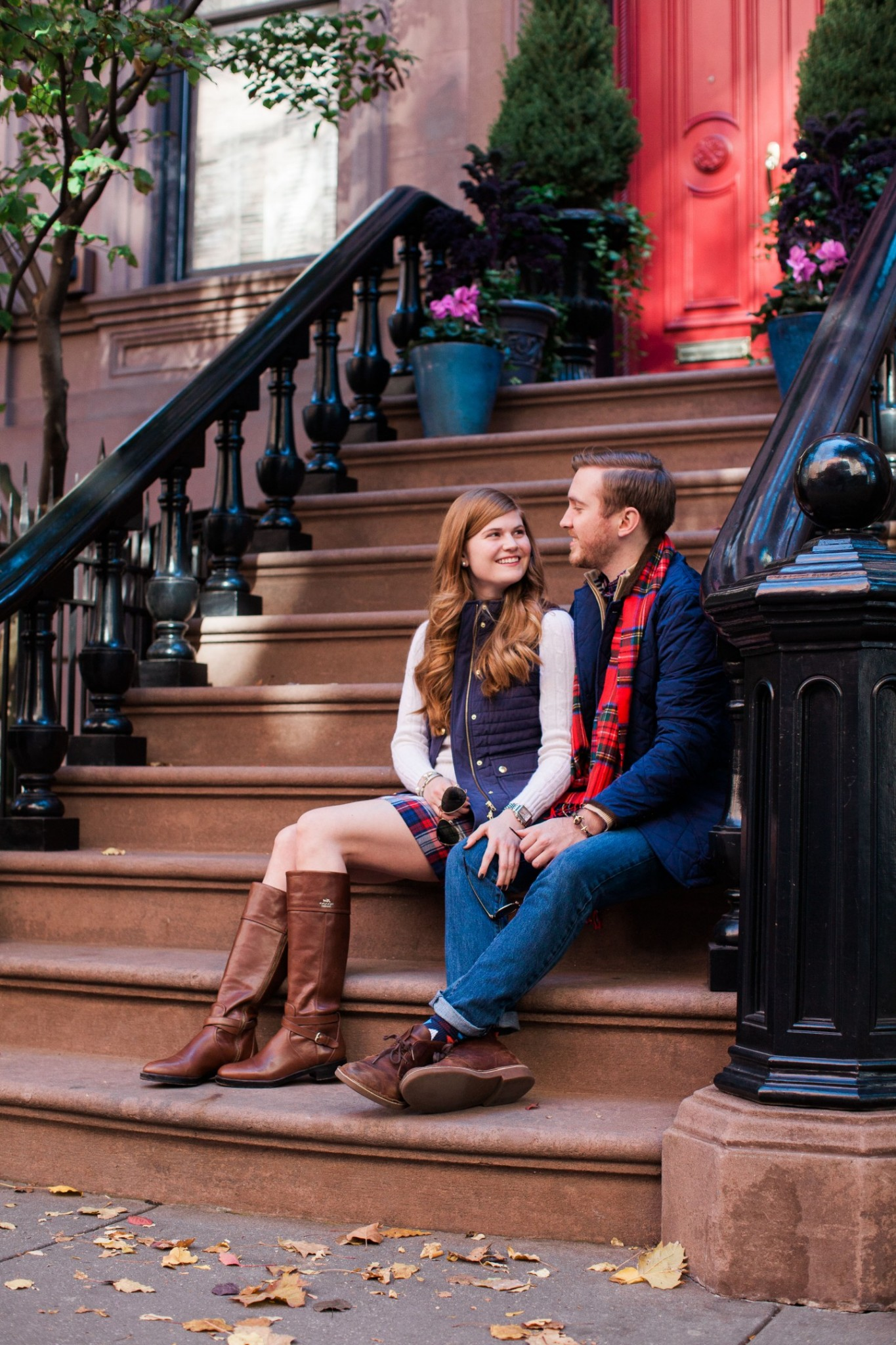 Lifestyle blogger Mollie Sheperdson shares a his and hers Vineyard Vines holiday look| His & Hers Matchy Holiday Outfits featured by top London fashion blogger, Mollie Moore: couple standing in front of a NYC entrance door wearing plaid accent pieces: a plaid scarf for him and plaid skirt for her