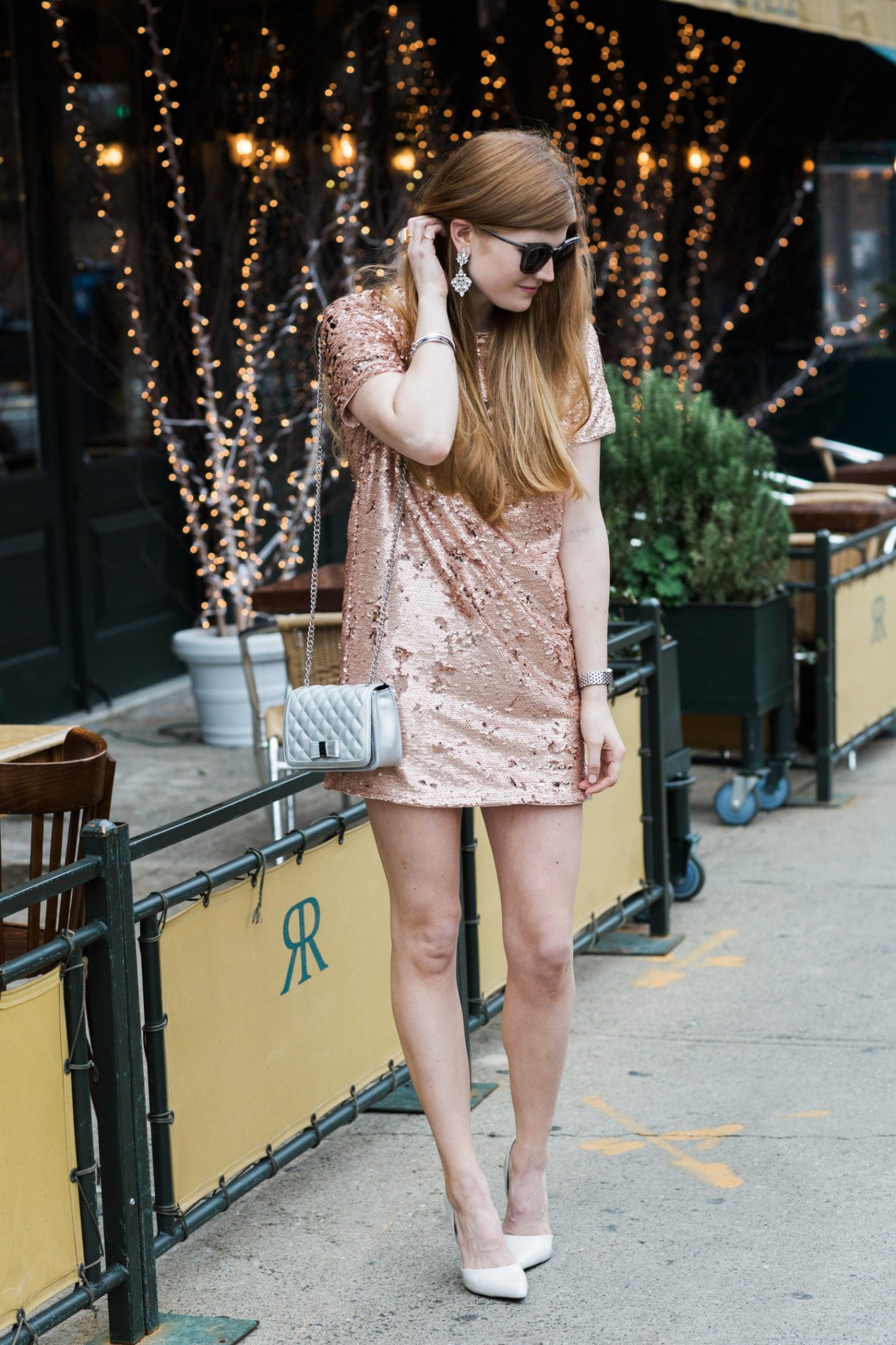 Top London fashion blogger, Mollie Moore, features 5 holiday looks to recreate year after year: picture of a woman wearing a sequin mini dress, black clutch, aviator sunglasses and metallic heels: pink sequin mini dress, white heels and teardrop earrings