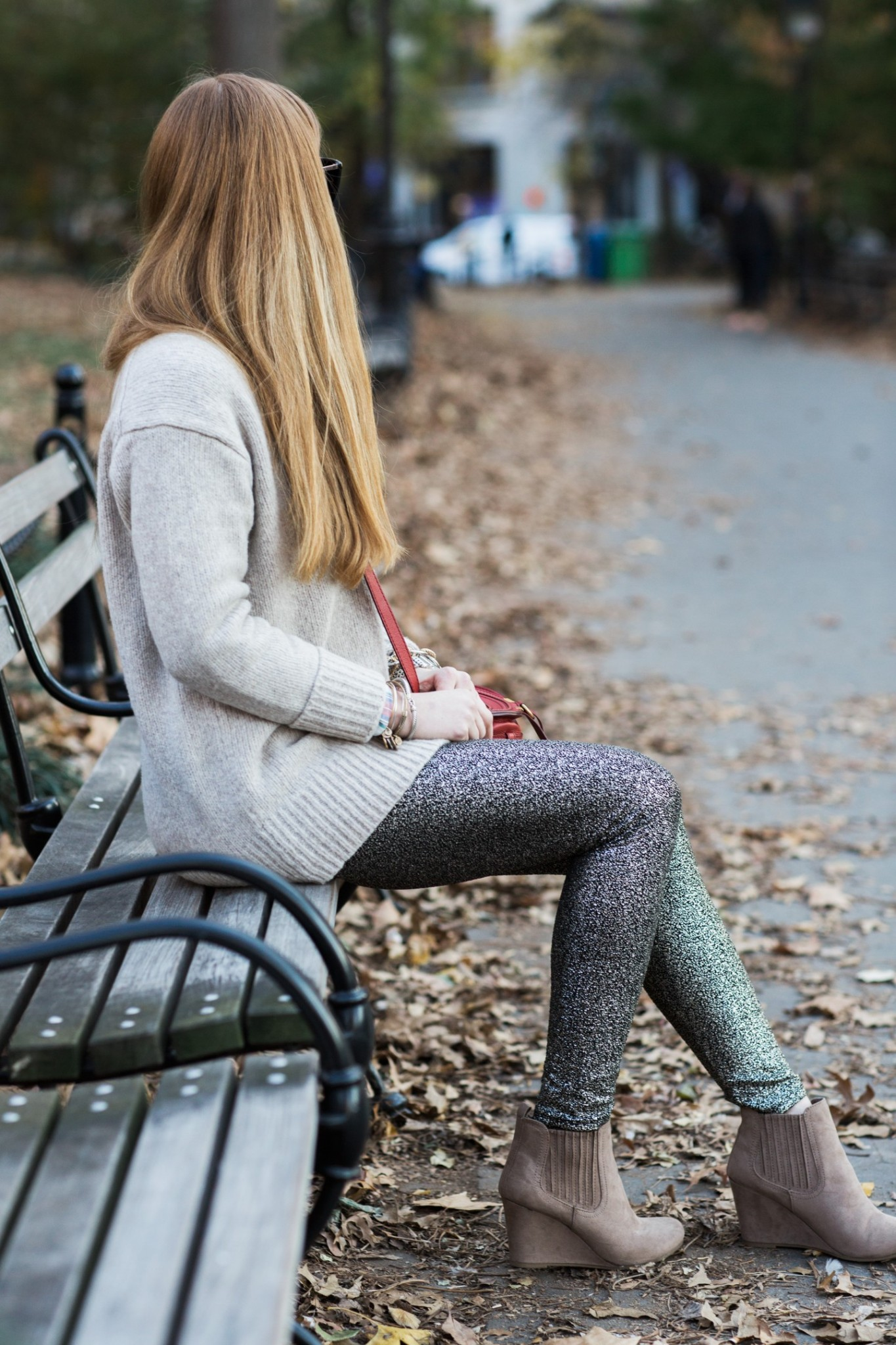 Top London fashion blogger, Mollie Moore, features 5 holiday looks to recreate year after year: woman sat on a bench wearing a cozy knit pullover, sequin leggings and a saddle crossover bag