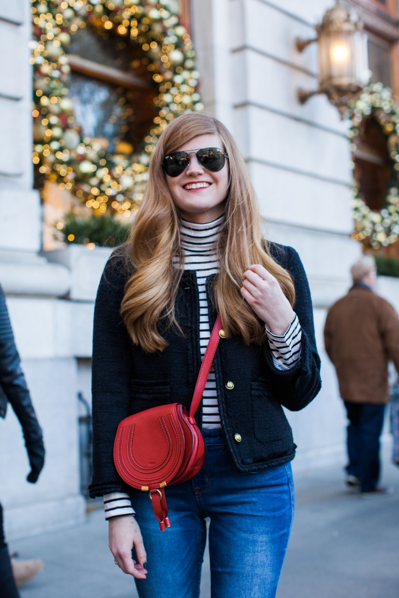 Top London fashion blogger, Mollie Moore, styles a festive look whilst spending Christmas at the Plaza in New York City: picture of a woman wearing Aviator sunglasses, Chloe crossover bag, skinny jeans, striped sweater, a black cropped jacket and plaid flats
