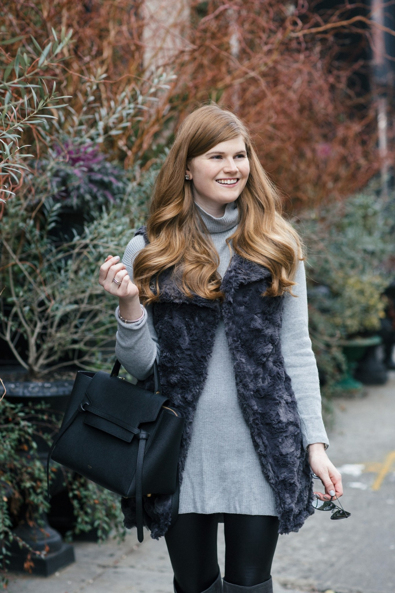 Lifestyle blogger Mollie Sheperdson styles a faux fur vest and OTK boots