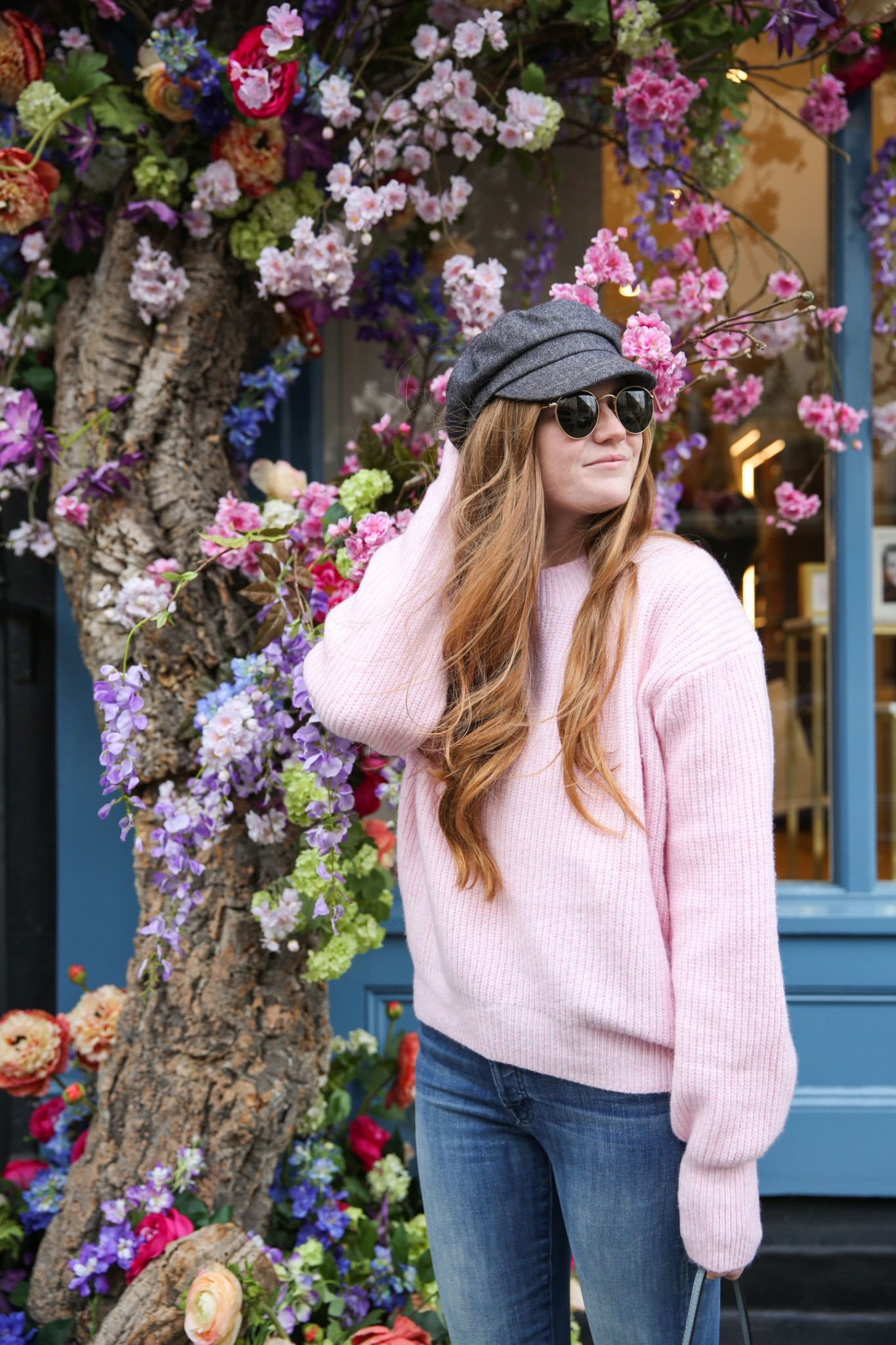 Spring Hats featured by top London fashion blogger Mollie Moore; Image of a woman wearing a hat, pink sweater, jeans and sneakers.