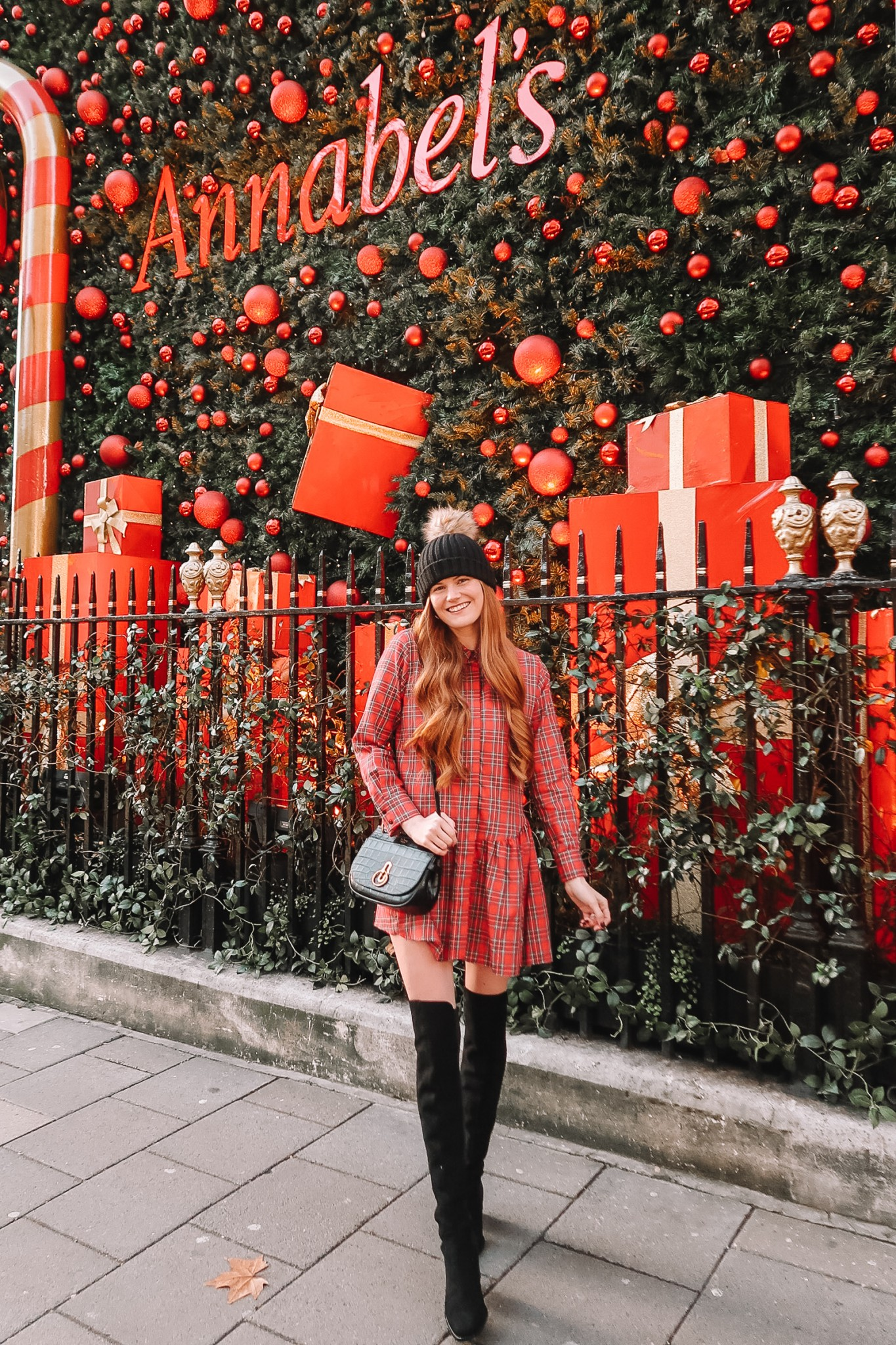 A Festive & Casual Christmas Eve Outfit featured by top London fashion blogger, Mollie Moore: image of a woman wearing a Vineyard Vines plaid dress, Marc Fisher Over the Knee Boots, Topshop Pompom beanie and Mulberry leather shoulder bag