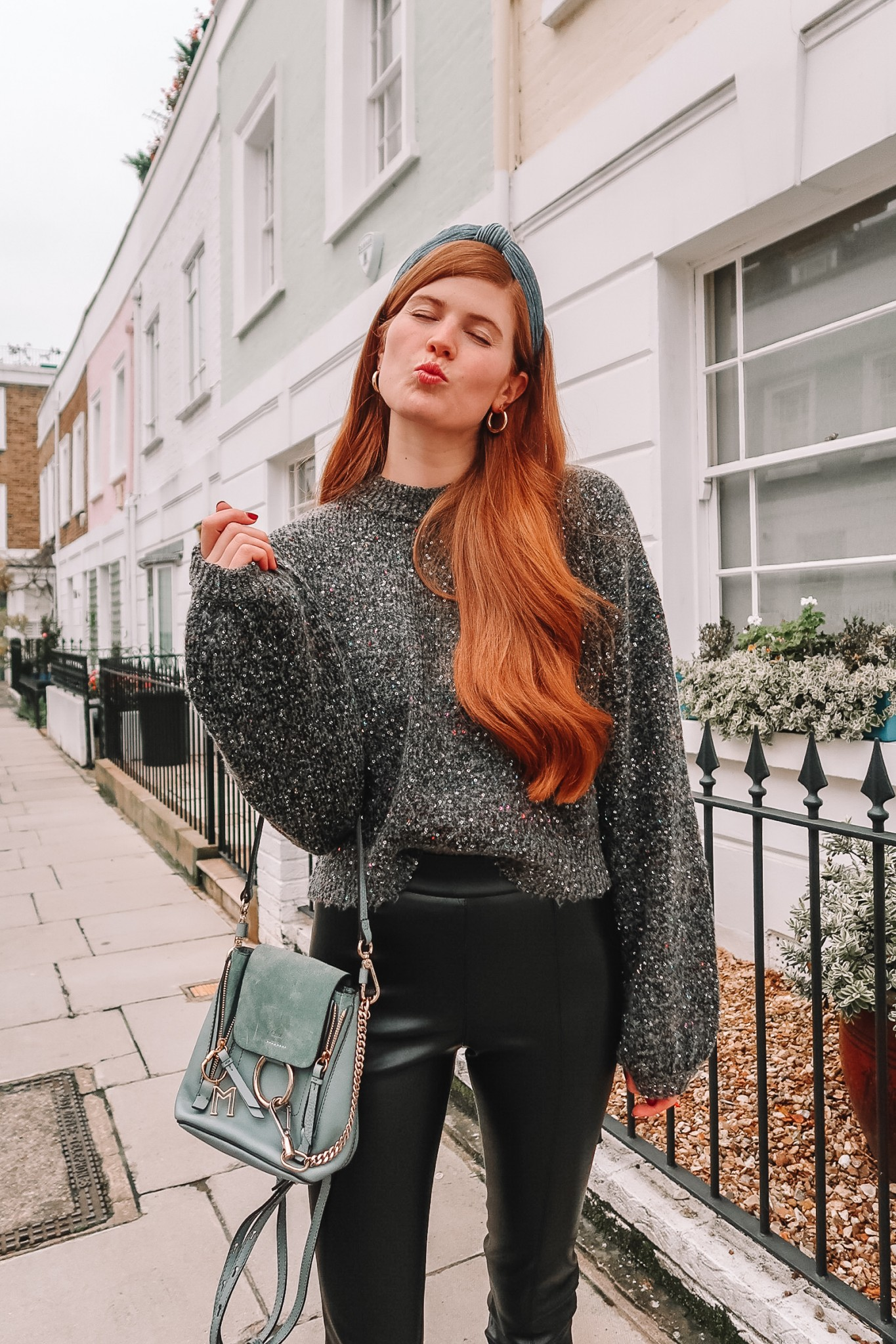 Chic and Cozy | Two NYE Outfit Ideas featured by top London fashion blogger Mollie Moore | 2 Stylish NYE Outfit Ideas featured by top London fashion blogger, Mollie Moore: image of a woman wearing a French Connection sequin sweater, Topshop faux leather skinny pants, & other stories suede booties, Chloe leather bag, Anthropologie head scarf and Halogen earrings