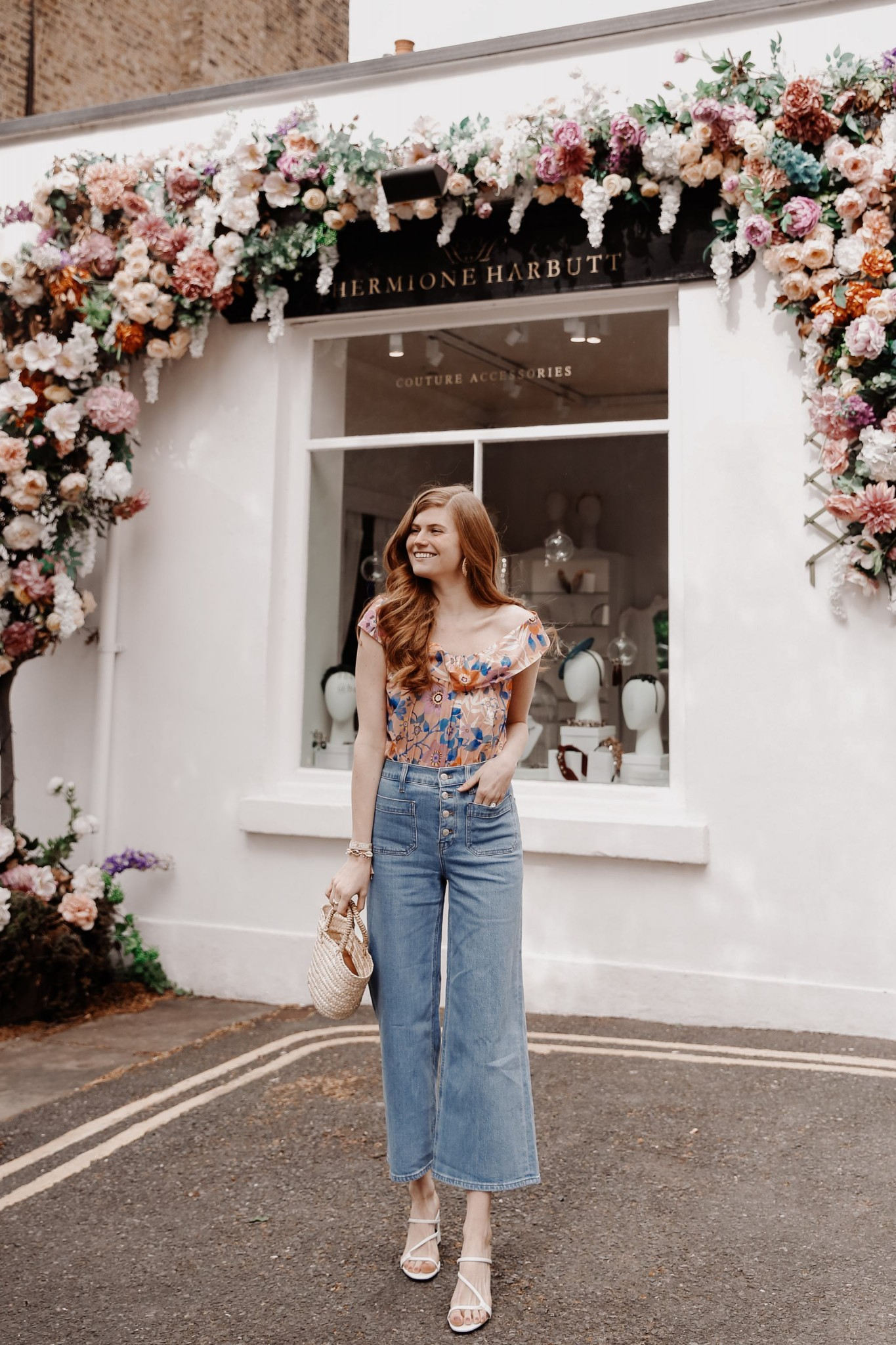 Casual Easter Outfit featured by top London fashion blogger Mollie Moore; Image of a woman wearing J.CREW X LIBERTY LONDON BLOUSE, POINT SUR WIDE-LEG JEANS, ZARA STRAPPY MULES, Mango MINI STRAW BAG, PUKA SHELL BRACELET and ALDO STRAW HOOP EARRINGS