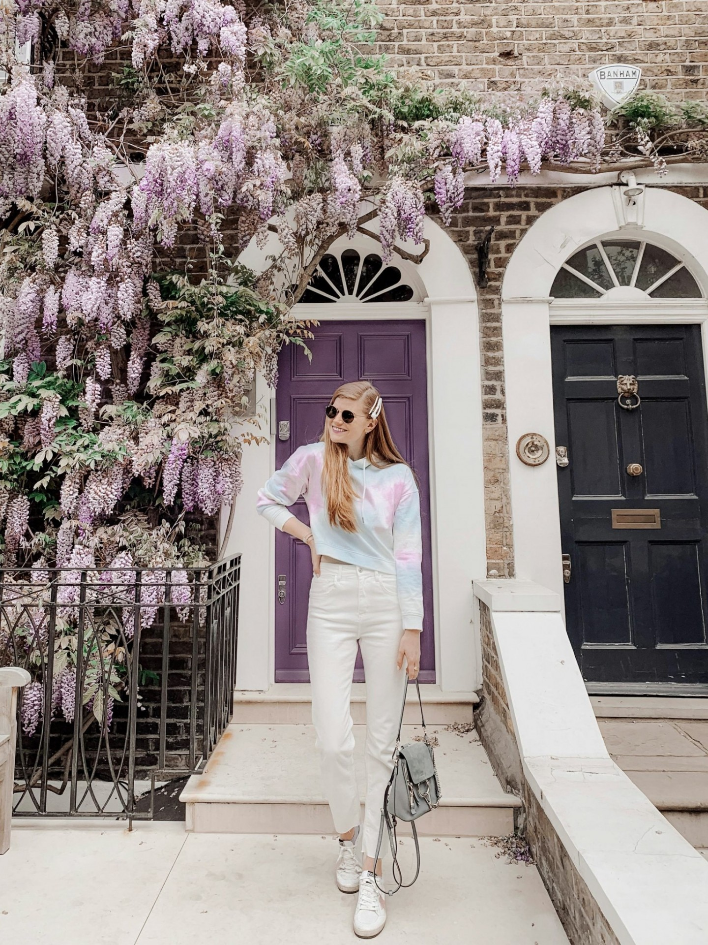 Spring Summer Trends featured by top London fashion blogger Mollie Moore; Image of a woman wearing white jeans, sneakers and a tie-dye hoodie.