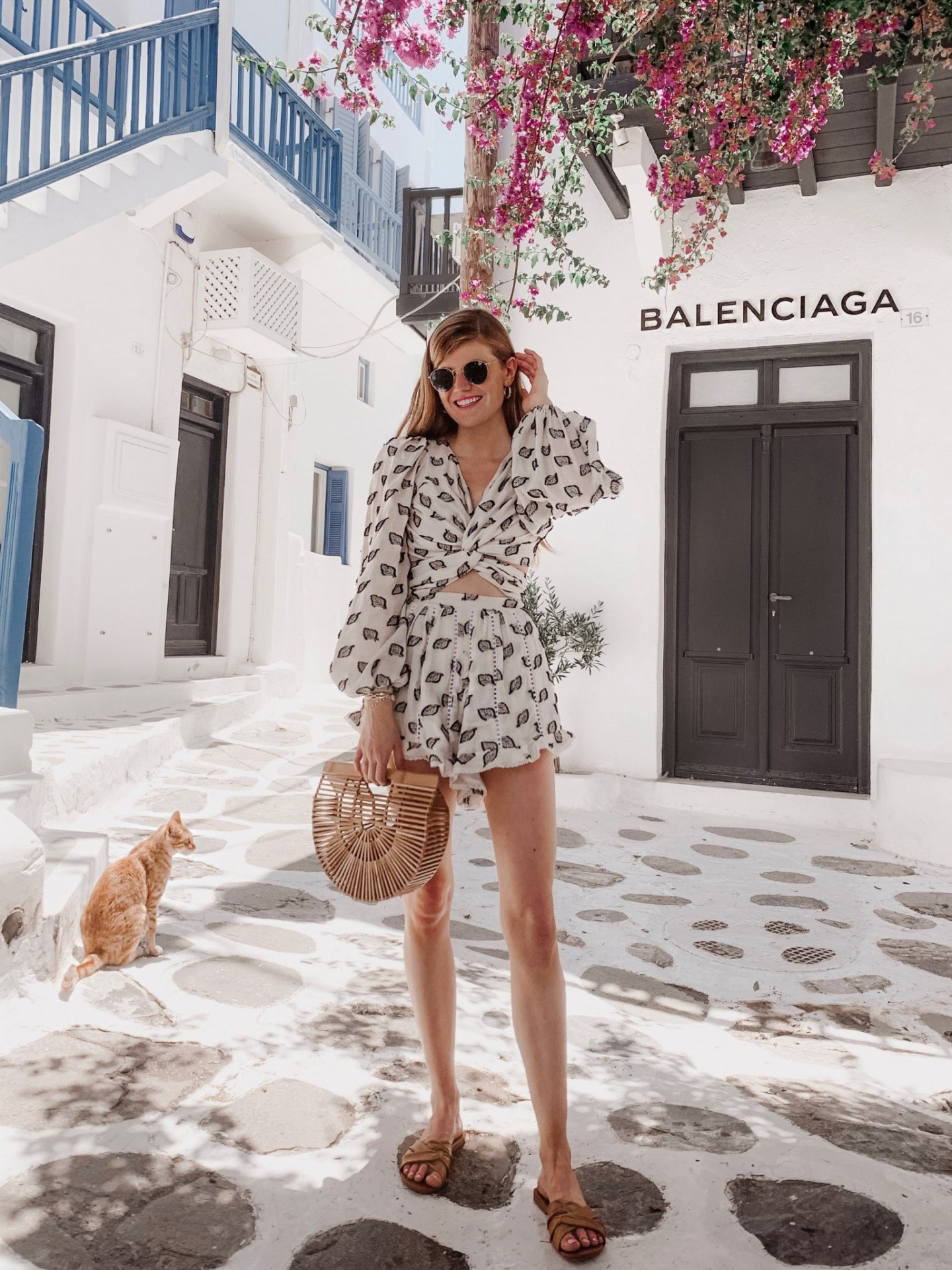 Mykonos Travel Guide featured by top London travel blogger Mollie Moore; Image of a woman wearing a two-piece black and white outfit.