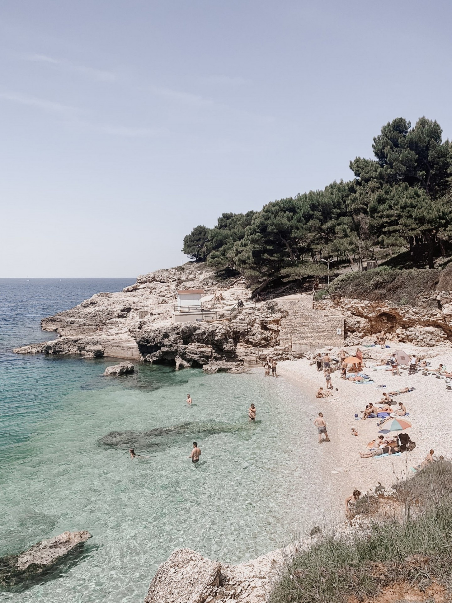 Lifestyle blogger Mollie Moore shares an Istria, Croatia travel guide. | Istria, Croatia Travel guide by popular London fashion and travel blogger Mollie Moore: image of people sitting on a beach and swimming in the Adriatic Sea in Istria, Croatia.