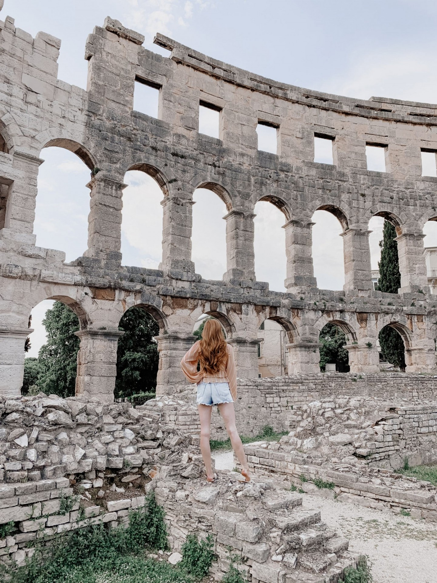 Lifestyle blogger Mollie Moore shares an Istria, Croatia travel guide. | Istria, Croatia Travel guide by popular London fashion and travel blogger Mollie Moore: image of woman standing in building ruins in Istria, Croatia.