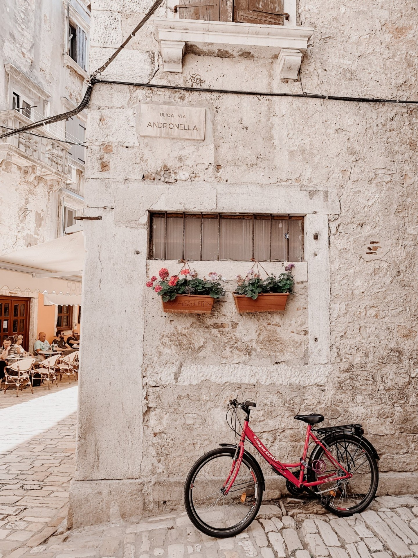 Lifestyle blogger Mollie Moore shares an Istria, Croatia travel guide. | Istria, Croatia Travel guide by popular London fashion and travel blogger Mollie Moore: image of a red bicycle leaning up against the side of the Ulica Via Andronella building in Istria, Croatia.