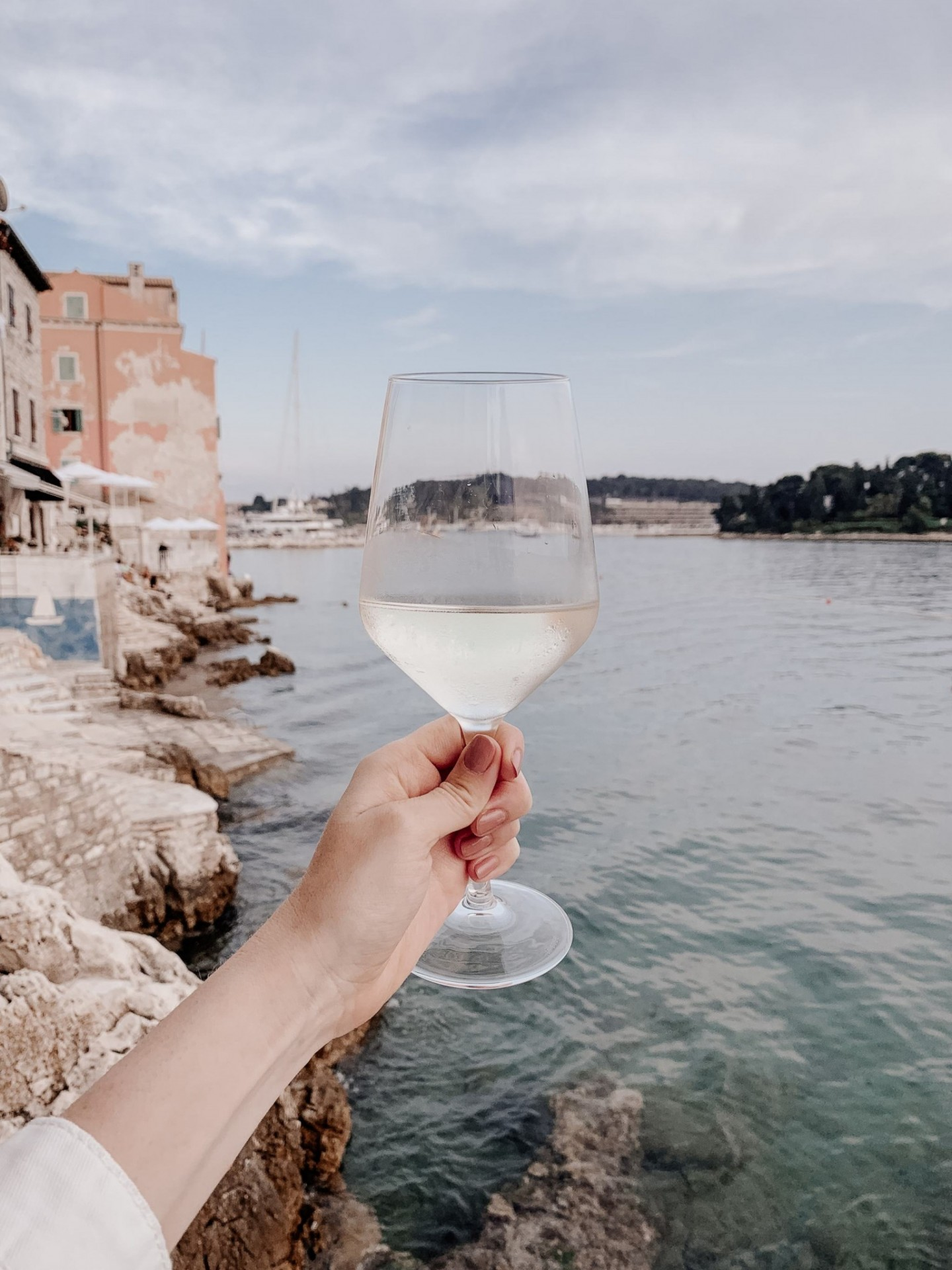 Lifestyle blogger Mollie Moore shares an Istria, Croatia travel guide. | Istria, Croatia Travel guide by popular London fashion and travel blogger Mollie Moore: image of a woman extending her arm out and holding a glass of white wine over the Adriatic Sea in Istria, Croatia.