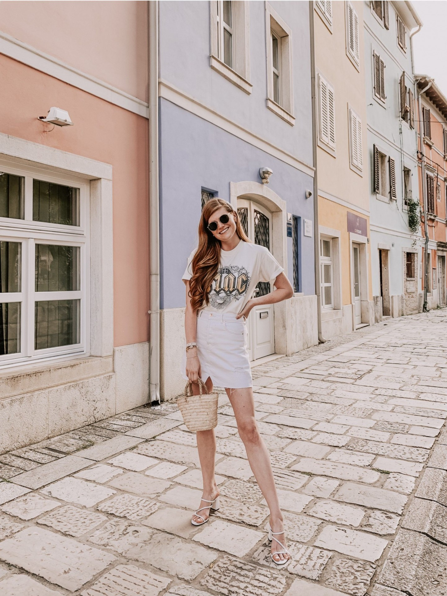 Lifestyle blogger Mollie Moore shares an Istria, Croatia travel guide. | Istria, Croatia Travel guide by popular London fashion and travel blogger Mollie Moore: image of a woman standing on a cobble stone street lined with pastel colored buildings in Istria, Croatia.