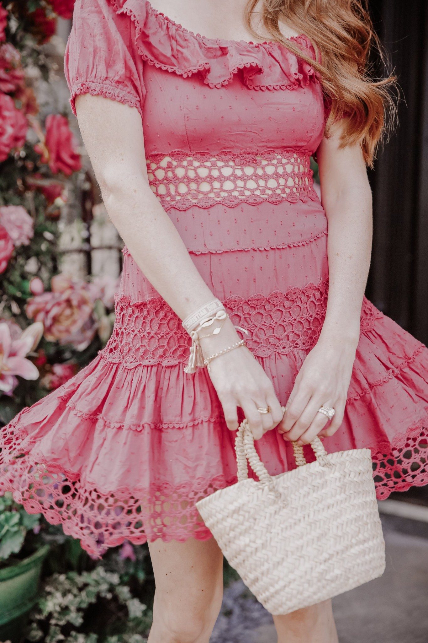 Lifestyle blogger Mollie Moore shares summer wedding outfit ideas | What to Wear for a Summer Wedding by popular London fashion blogger Mollie Moore: image of woman standing under a floral archway and wearing Orelia gold plated cowrie shell huggie hoop earrings, set of Christian Dior J'adior bracelets, Mango braided mini bag, and Shopbob Free People Cruel Intentions Mini Dress.