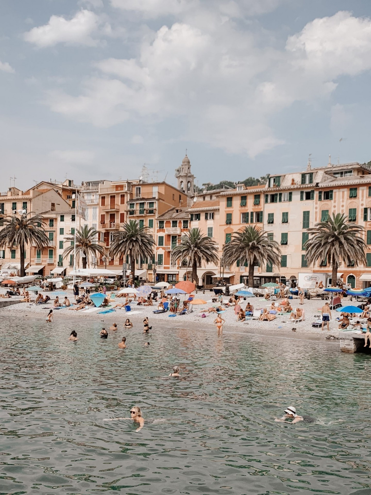 Lifestyle blogger Mollie Moore shares a Portofino Travel Guide | Travel Guide: Best Things to do in Portofino Italy by popular international travel blogger, Mollie Moore: image of people at the beach in Portofino Italy.