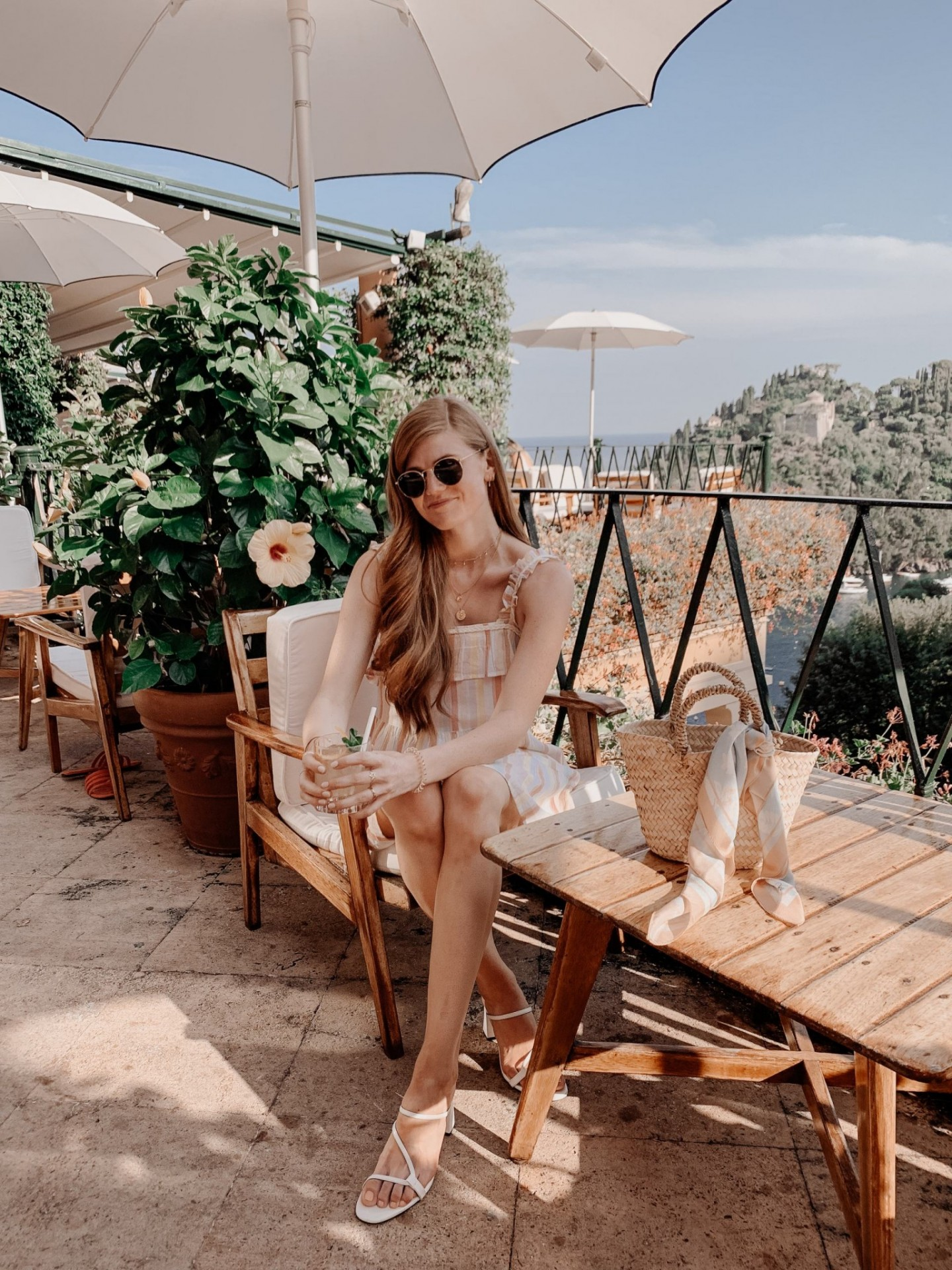 Lifestyle blogger Mollie Moore shares a Portofino Travel Guide | Travel Guide: Best Things to do in Portofino Italy by popular international travel blogger, Mollie Moore: image of a woman sitting outside in Portofino Italy.
