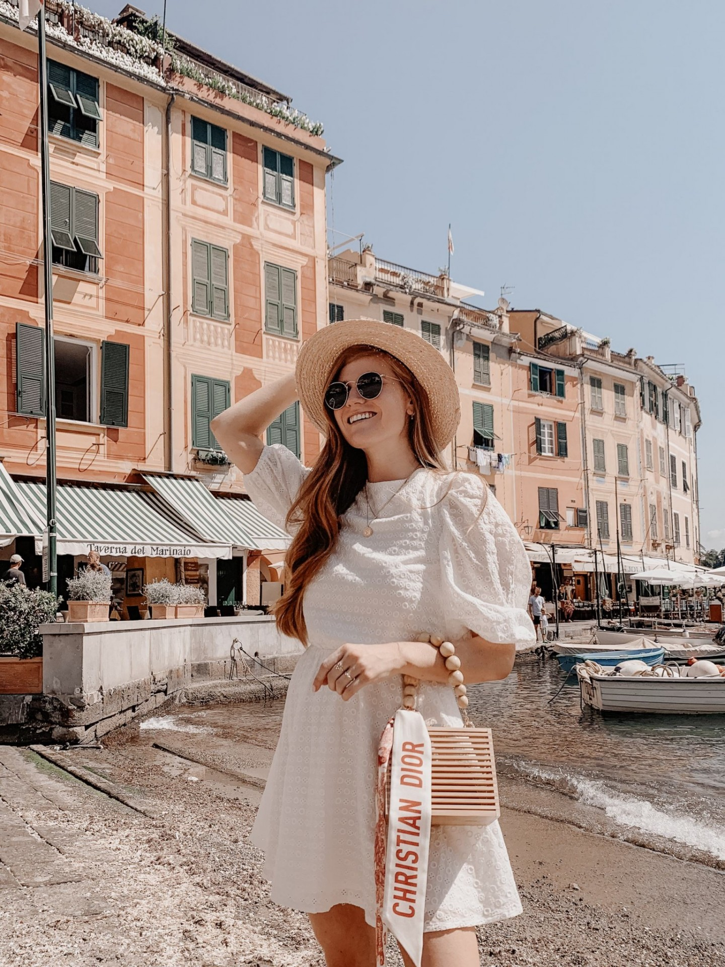Lifestyle blogger Mollie Moore shares a Portofino Travel Guide | Travel Guide: Best Things to do in Portofino Italy by popular international travel blogger, Mollie Moore: image of a woman standing by the ocean in Portofino Italy.
