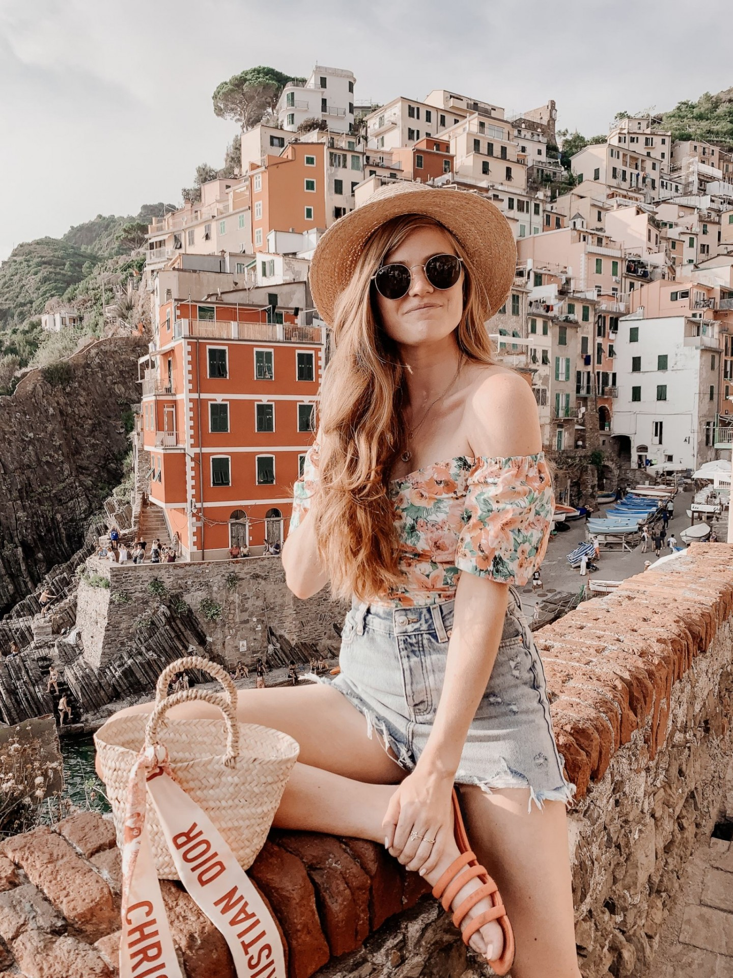 Lifestyle blogger Mollie Moore shares a Cinque Terre travel guide | Travel Guide: Things to do in Cinque Terre, Italy by popular London travel blogger, Mollie Moore: image of a woman sitting outside on a stone wall with the city of Cinque Terre, Italy in the background.