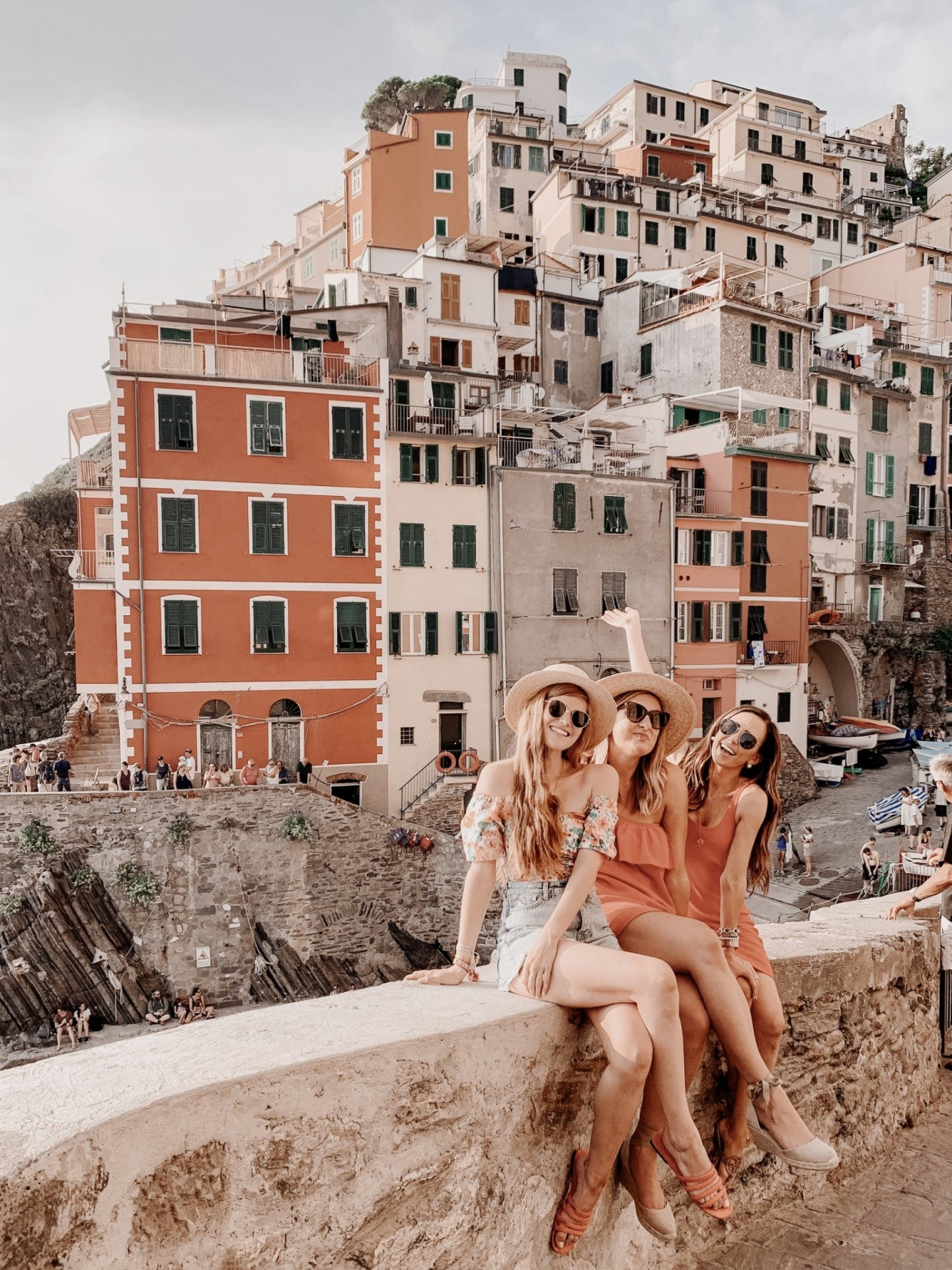Lifestyle blogger Mollie Moore shares a Cinque Terre travel guide | Travel Guide: Things to do in Cinque Terre, Italy by popular London travel blogger, Mollie Moore: image of three women sitting together on stone wall with the city of Cinque Terre, Italy in the background.